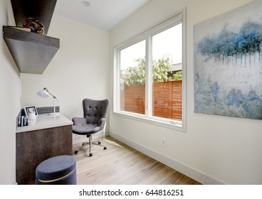 Light small home office interior with corner desk and grey upholstered chair on hardwood floor. Northwest, USA