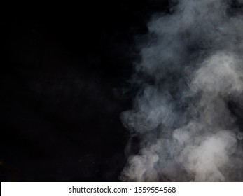 Light smoke texture on a dark background. Studio photography