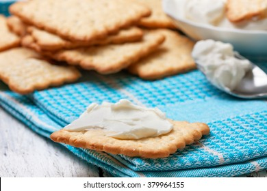 light snack of crackers and cream cheese on blue napkin