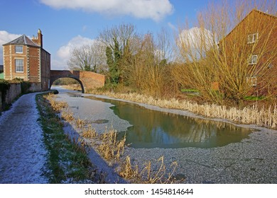 A light snow on the Stroudwater, Thames and Severn Canal as it flows through the Stroud Valley looking towards Nutshell house, Stonehouse near Stroud, The Cotswolds, Gloucestershire, England, UK