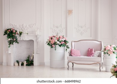 Light sofa with pink pillows stands in the interior light studio room near the romantic fireplace decorated with spring flowers, wreath, candles