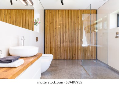 Light and spacious bathroom with walk in shower, mirror, wooden worktop with basin and wood wall divider