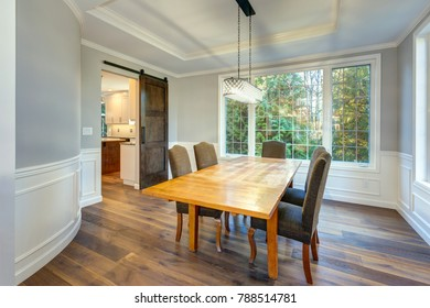 Light and spacious dining room interior in a luxury custom built home. White wainscoting surrounding a light wood table and grey parsons chairs placed under rectangular tray ceiling.