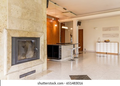 Light and spacious living room with travertine fireplace and open kitchen