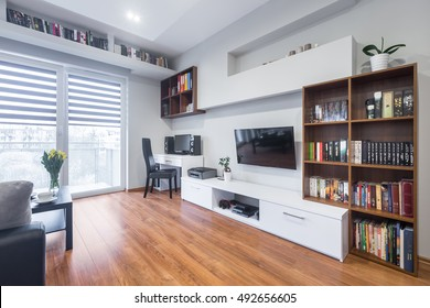 Light and spacious living room with window, TV, bookshelves, floor panels and modern furniture