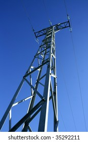 Light steel electricity tower pole over vibrant blue summer sky