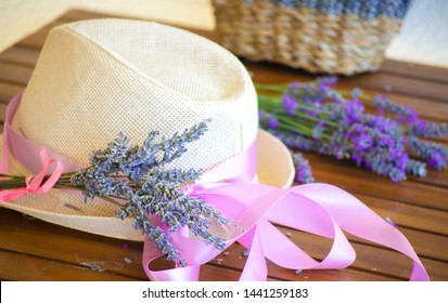 Light straw hat on wooden brown table. Lilac-pink ribbon on hat of woman's hat. A bouquet of dry lavender in rustic wicker straw basket.