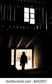 Light streaming through the slats of a barn, silhouette of a boy in the entrance.