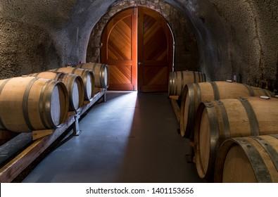 Light Streaming Through Wine Cellar Door with Oak Wine Barrel Casks on Racks