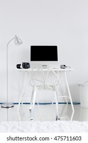 Light study room with floor lamp, white desk, crystal chair and computer