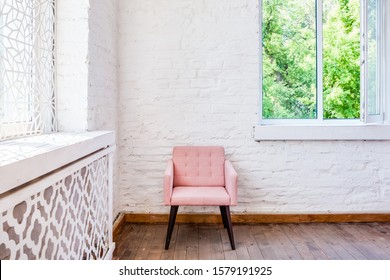 Light sunny interior with white brick wall, pink chair and open window with garden view