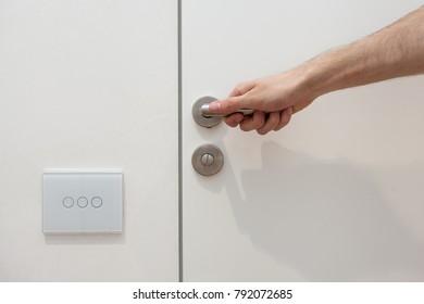 Light switch next to the door handle. Open white door with metallic handle. The man opens the door
