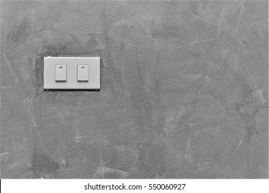 Light switch on concrete wall background with copy space.