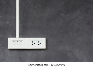 light switch and outlet plug on concrete wall
