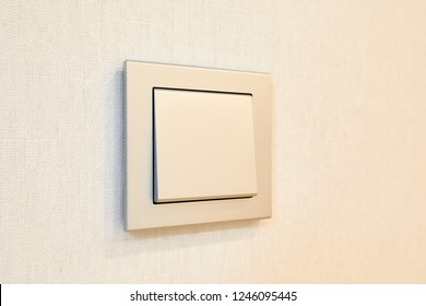 a light switch, a plastic mechanical switch installed on a light gray wall.