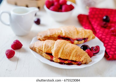 Light and tasty breakfast or lunch, croissants with berry jam, fresh raspberries, cherries, strawberries, black coffee and milk on a light background