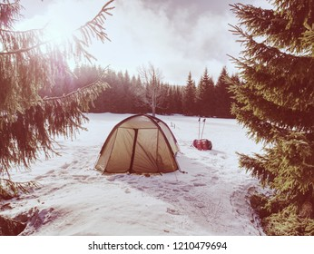 Light tent set on the snow in the winter forest in the mountains. Oversleep in snowy landscape.