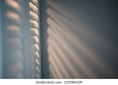 Light throo louvers  on grey wall