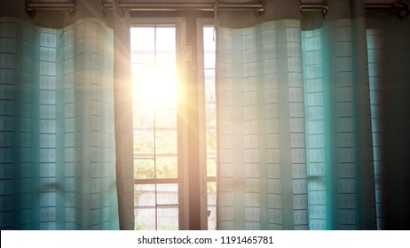 Light through windows and blue curtains.