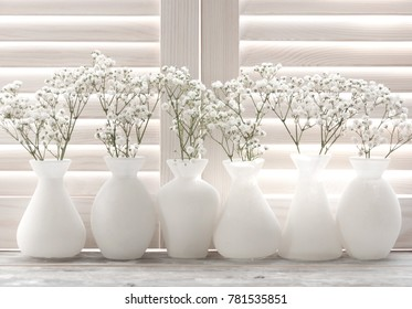 Light through the wooden shutters and blinds.Small white flowers on a white background. Soft home decor. Gypsophila flowers. White flowers in a vase. Retro style.