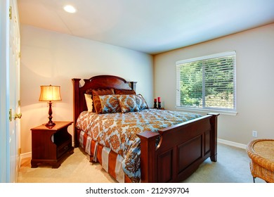 Light tones bedroom with rich wood carved bed and nightstands