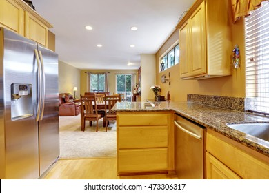 Light tones kitchen interior with modern steel double doors fridge. Polished Granite counter tops. Dining room view. Northwest, USA