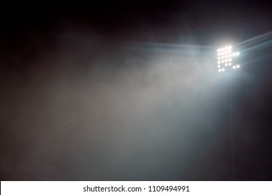 Light tower lit at a stadium during nightime. Stadium lights against dark night sky background. stadium lights and smoke.