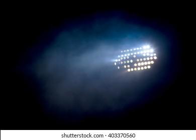 Light tower lit at a stadium during nightime.