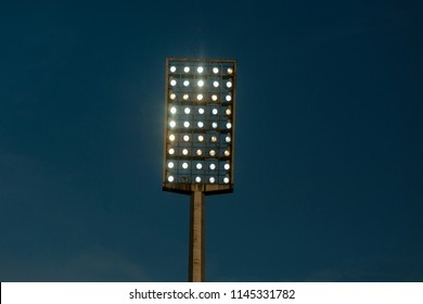 Light tower reflectors at a stadium during nightime.