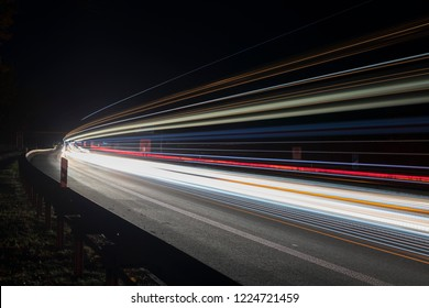 Light tracks of passing cars at night on a German motorway at the Lübbenau exit