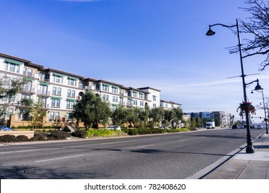 Light traffic on a street in Santa Clara on a sunny day, multifamily housing development on the side of the road; San Francisco bay area, California