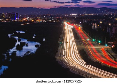 Light trails from busy traffic on Lincoln Boulevard, water reflecting the sky in Ballona Wetlands, and the Santa Monica Mountains in the background after sunset, Playa Vista, California