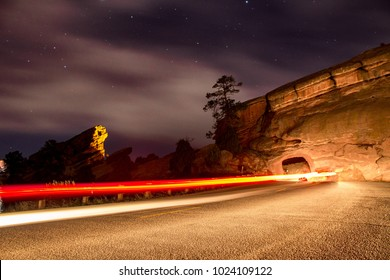 Light trails of a car passing through a tunnel at Red Rocks Park and Ampitheater outside Denver Colorado
