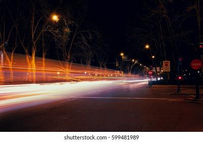 Light trails caused by traffic on the Paseo de Prado, Madrid, Spain