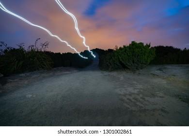 Light trails of couple walik or trekking past on top Mount Maunganui on dark night