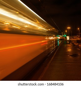 light trails of a driving tram at night