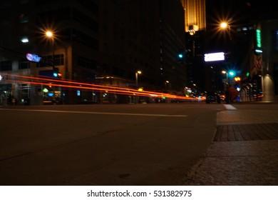 Light trails at night through downtown Minneapolis Minnesota. Brake and headlights streak glows down busy city street