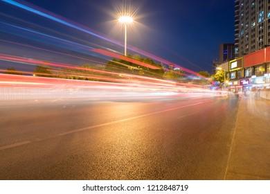 light trails on city street, urban night scene