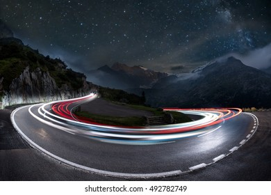 light trails on a hairpin bend and milky way in the background. swiss alps pass road at night, starry sky with galaxy and car light trails