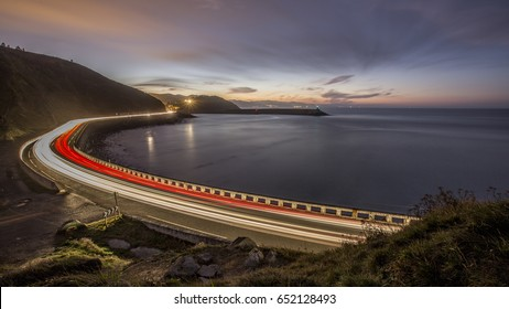 Light Trails On Highway By Sea Against Sky During Sunset, Zumaia