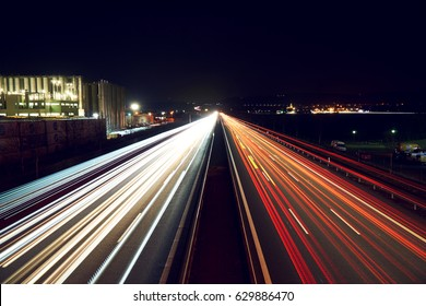 Light trails on highway with a industry building - slightly toned.