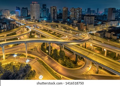 light trails on highway intersection and overpass with modern cityscape at night