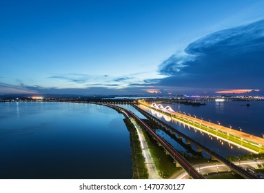 light trails on the railway and road bridge, night falls over the lake in jiujiang city, China