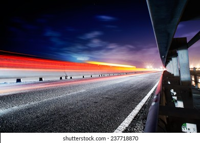 Light trails on the road to the side of the guard rail