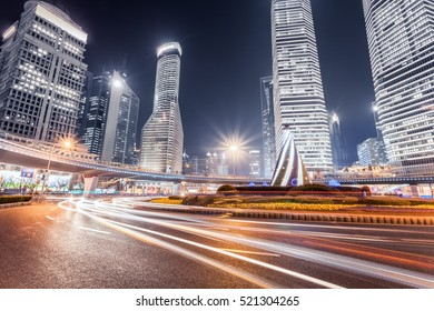 light trails on the roundabout with modern financial buildings in shanghai at night