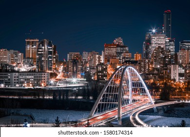 Light trails on the Walterdale Bridge, in Edmonton, Alberta. The lit up city skyline is visible in the background and the sky is a dark blue. Blue and Orange tones.
