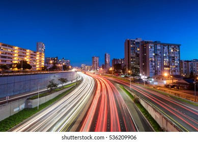 Light trails over H1 highway in downtown Honolulu, Hawaii at blue hour
