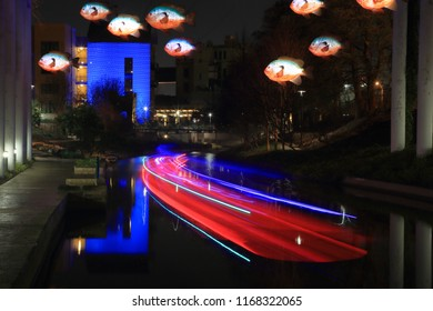 Light trails from a passing water taxi on the San Antonio River beneath the I-35 overpass with Donald Lipski Sunfish art installation overhead. San Antonio, TX, USA - February 24, 2018