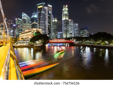 Light trails of tour boat on the Singapore river with the skyscraper of the financial district at night in Singapore in Southeast Asia