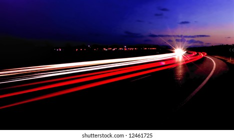 Light trails from two way traffic streaming along a highway at night.